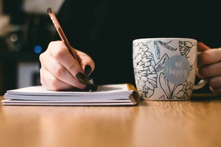 a-woman-with-black-nails-writes-in-a-notebook-with-coffee-cup-beside-her